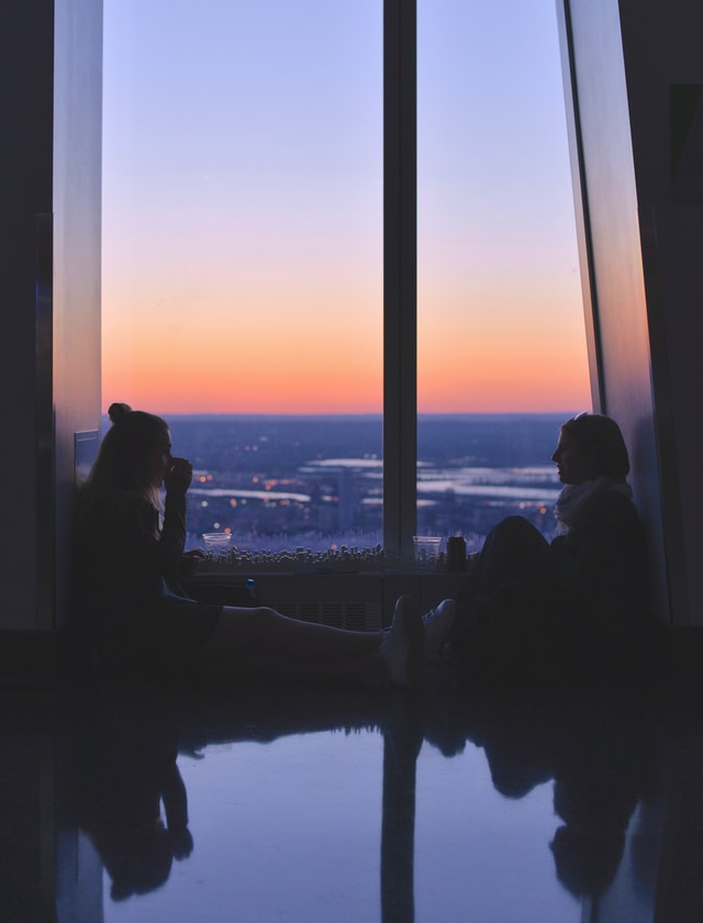 Two girls are sat at a window, both facing each other and engaging in conversation. The sky outside is blue and the fades to orange.