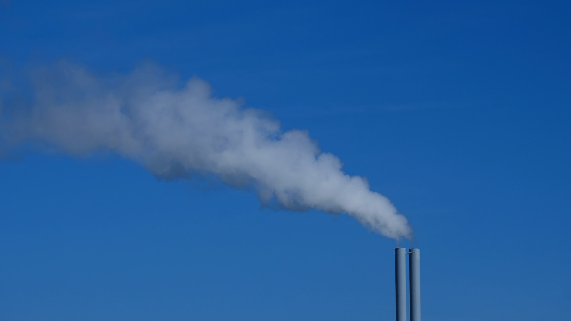 while the sky is a bright blue, gases that pollute the air are being released from two grey chimneys.