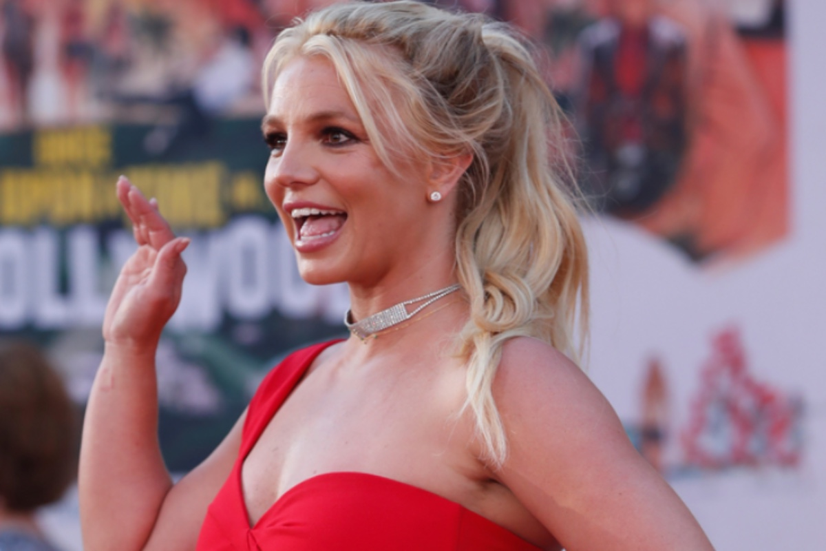 This image shows Britney Spears in a red, one-shoulder ballgown smiling away from the camera. She has one arm raised as though she is waving.