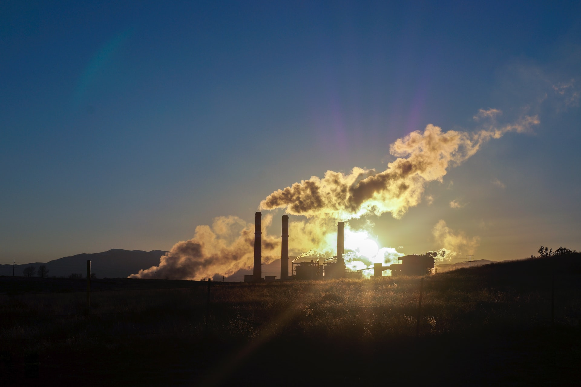 As the sun sets on the horizon, clouds of carbon dioxide are swept into the air. The CO2 is coming out of thin, dark towers.