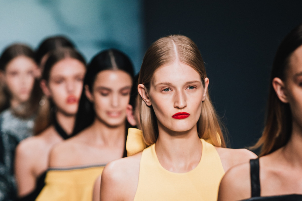 This image shows an over the shoulder displaying a row of woman walking a catwalk show. The first woman we see is in the centre of the frame wearing a yellow top.