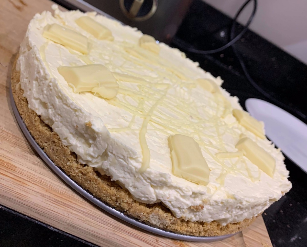 This image shows a milkybar cheesecake, on top of a wooden tray.