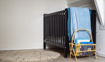 This image shows a baby's crib, the crib is black. There is a blue blanket laid over the edge of the crib and a cream-coloured rug on the floor.