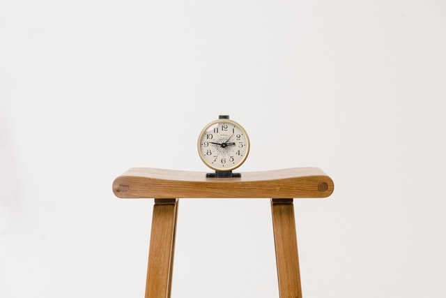 sat on a wooden stool is a small table clock. The clock is showing the time 14:46.