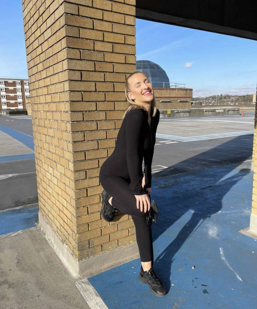 Here we see Alise Murray in a car park sporting an all black outfit as she playful poses leaning one leg on a pillar behind her.
