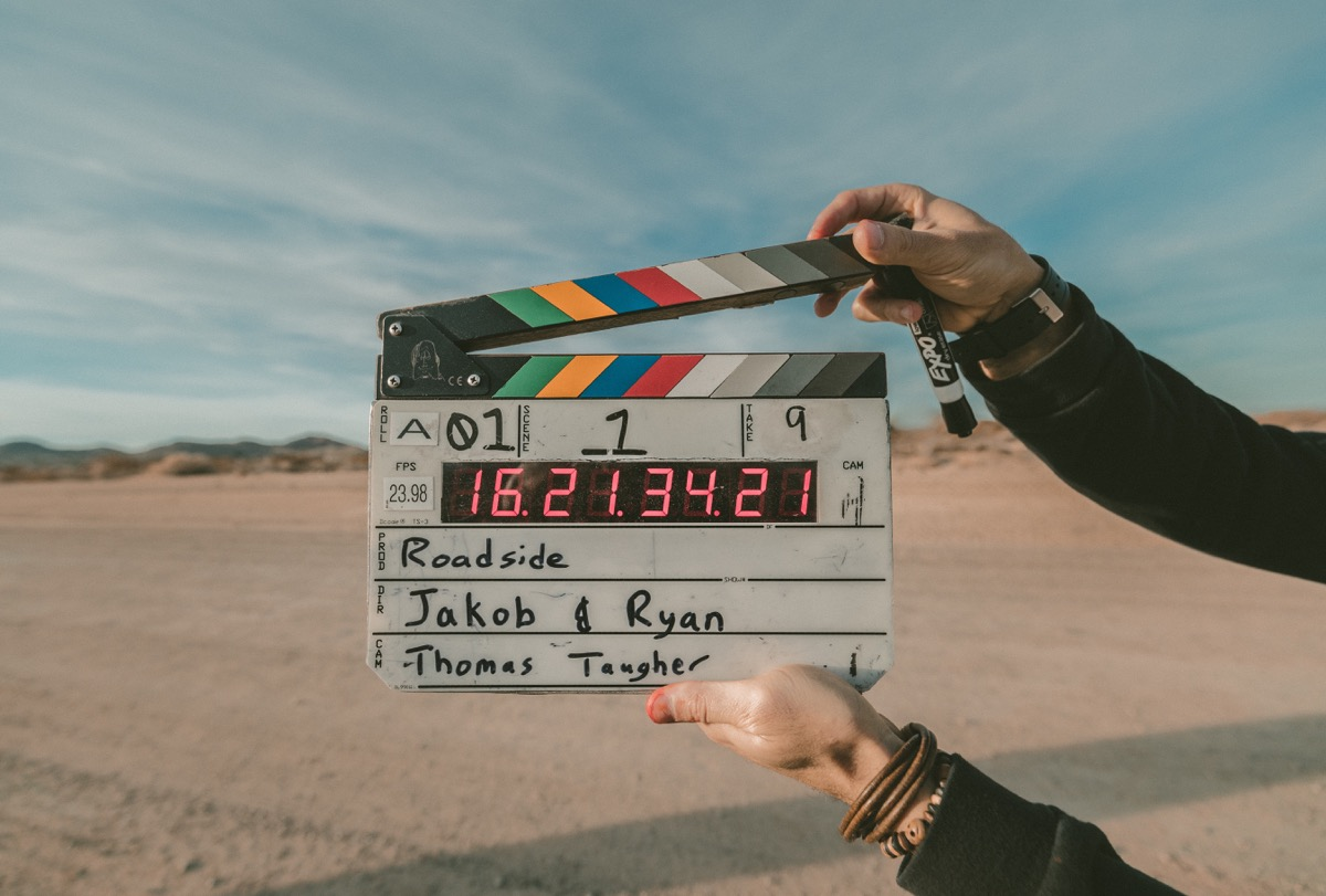 This image shows a film clapperboard being held up in the midst of the image. The background appears to be showing a desert with blue skies.