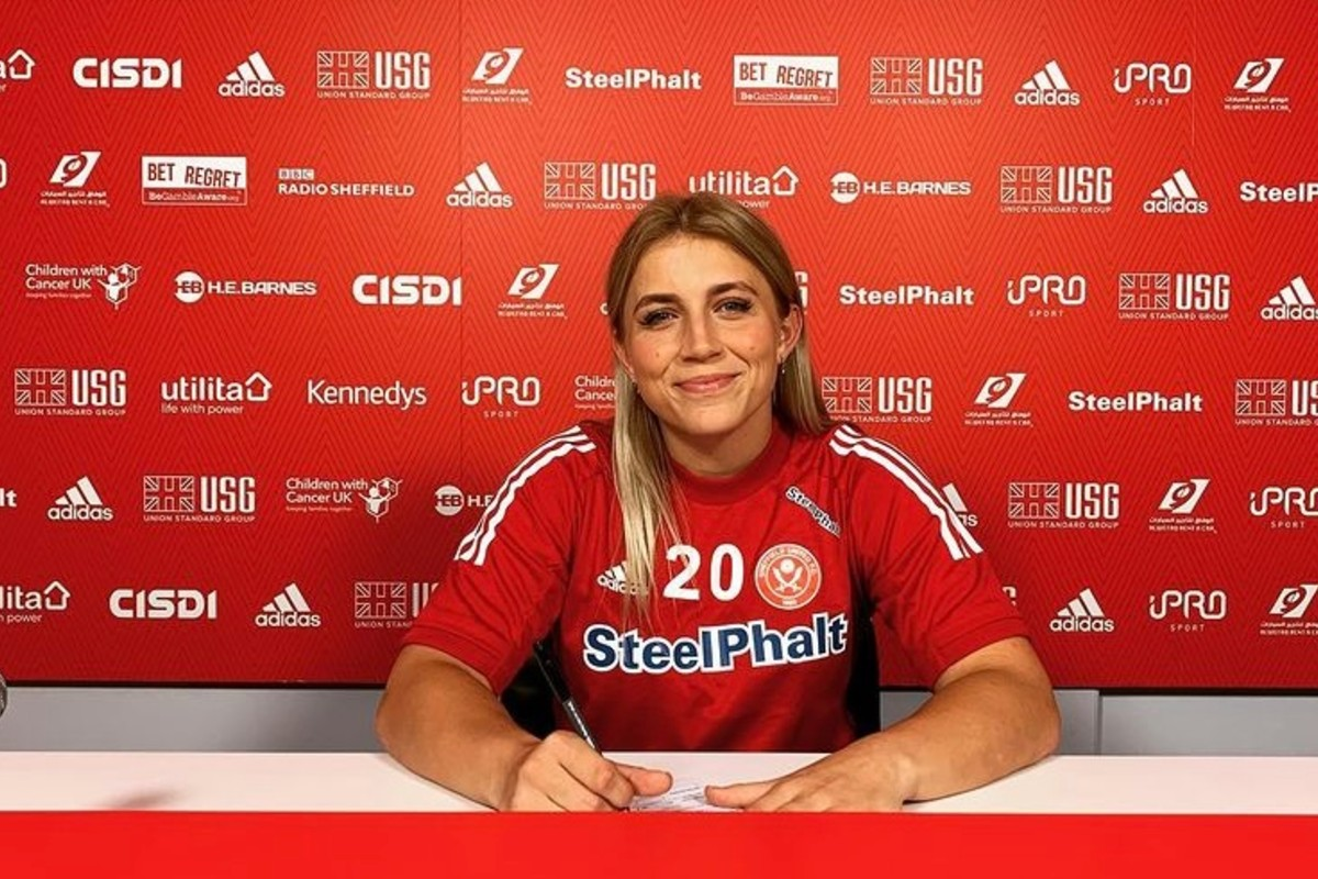 Frances Kitching sits at a table after signing for Sheffield United Women's team. The background behind her is bright red.