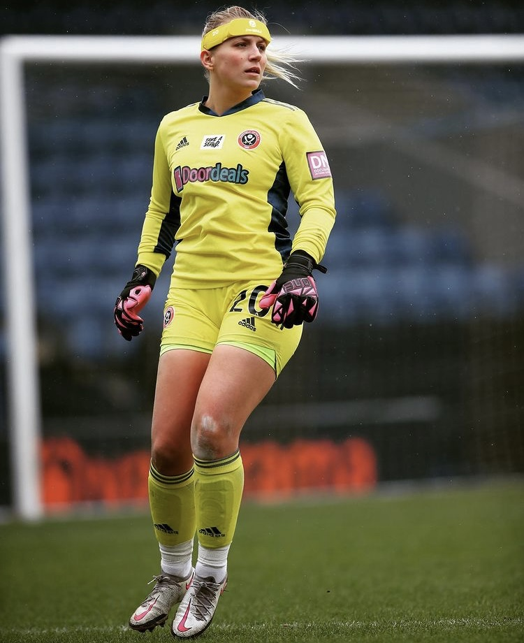 A photo of Frances when she is playing on the field. She is stood in front of the football nets and is wearing a bright yellow football kit. As well as a yellow headband, black goalkeeping gloves and white football trainers.