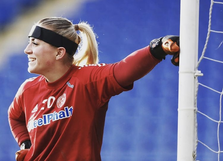 Another photo of Frances on the field. She is wearing a red football kit with a black headband. In a casual stances, she is leaning against a football net with one arm. The other arm is at her hip.
