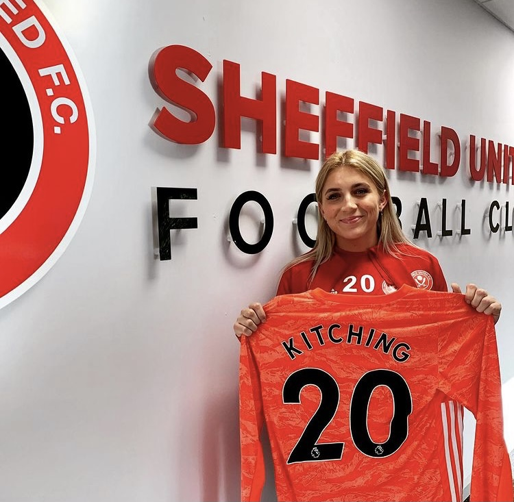 """Frances is stood in a Sheffield United Women's jersey whilst holding her red, long-sleeved football top in her hands. On the football top, her last name """"Kitching"""" and the number 20 is printed in black, bold writing. Behind her is the Sheffield United football club logo on a wall."""
