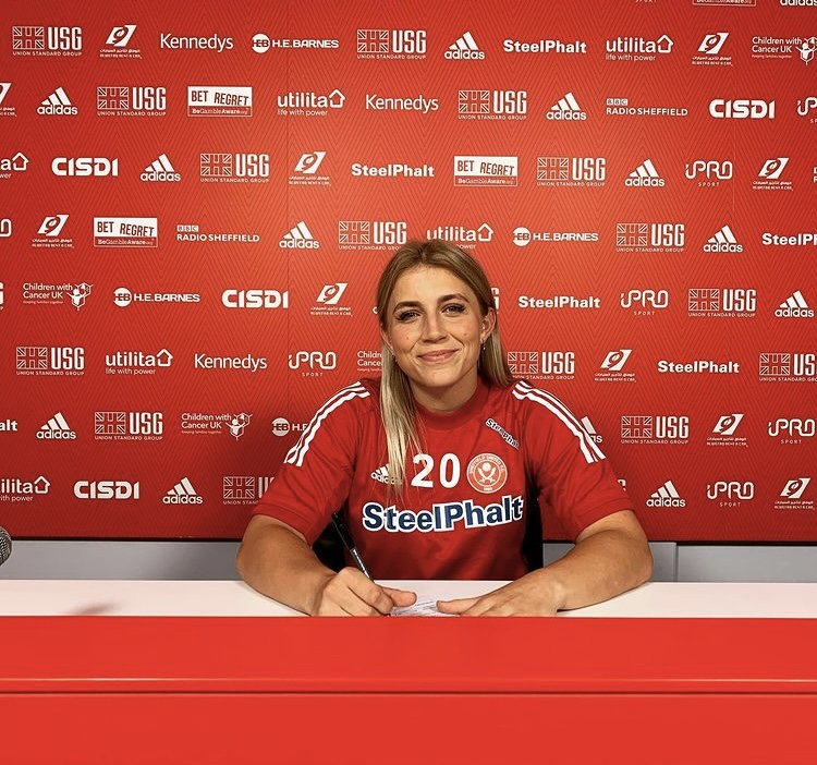 In this photo, Frances is sat at a white desk, posing for a photo after signing to be a player at Sheffield United Football Club. Behind her is a bright red wall that has numerous sports logos on.