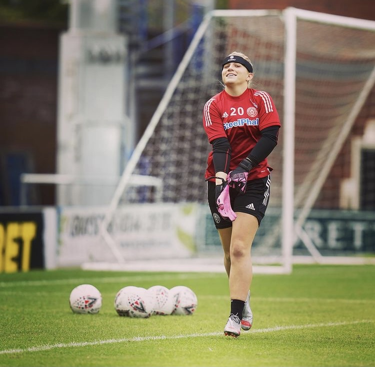 A more casual photo of Frances on the field. She is walking to the side of the pitch, wearing a red football top with a long-sleeved black top underneath and black shorts. She is slightly looking at the camera, smiling whilst pulling her goalkeeping gloves on. Behind her, next to the net, are numerous footballs in a group on the pitch.