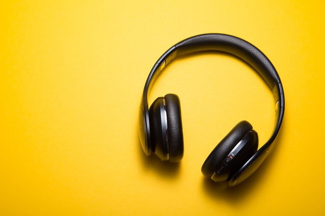 Against a bright yellow background, a black pair of headphones lay.
