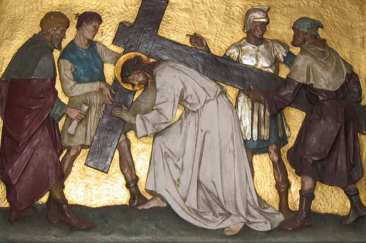 An old painted picture of Jesus carrying his cross to the hill where he would be crucified. Around him are a group of men, one of them is helping him carry the cross.