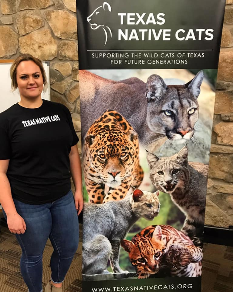 Kelsey Bernard is stood in a black top and blue jeans. Kelsey is stood next to a sign that has images of numerous big cats on it.