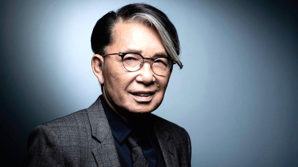 A photo of Kenzo Takada. Takada is wearing a black shirt, black tie and dark grey blazer.