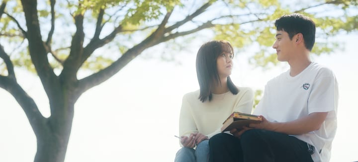 The image is very peaceful with a bright, clear sky and a blooming tree in the background. Sat on a bench is Kim Jojo and Hye-young are sat on a bench, both wearing jeans and a white top.