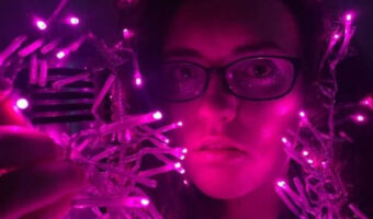 This image shows Lucy Crisp with pink fairy lights in the picture surrounding her.