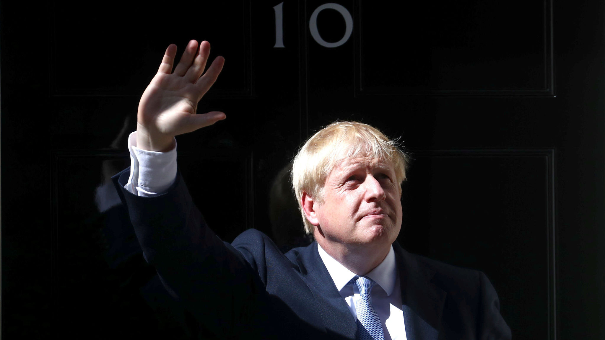 This image shows Boris Johnson standing and waving outside of 10 Downing Street when he was elected the new primeminster of the UK in 2019.