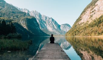 This image shows a man meditating at the end of a wooden walkway. The walkway leads to a vast surface of water. In the landscape, there are rowing mountains.