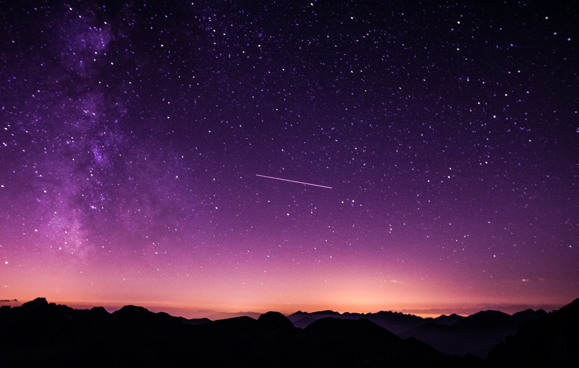 Above a dark landscape is a pink and purple sky. In the ski there are many stars illuminating along with a meteor.