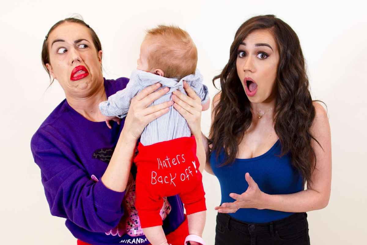 This image shows YouTube star Colleen Ballinger, character Miranda Sings and a baby. Miranda is holding the baby.
