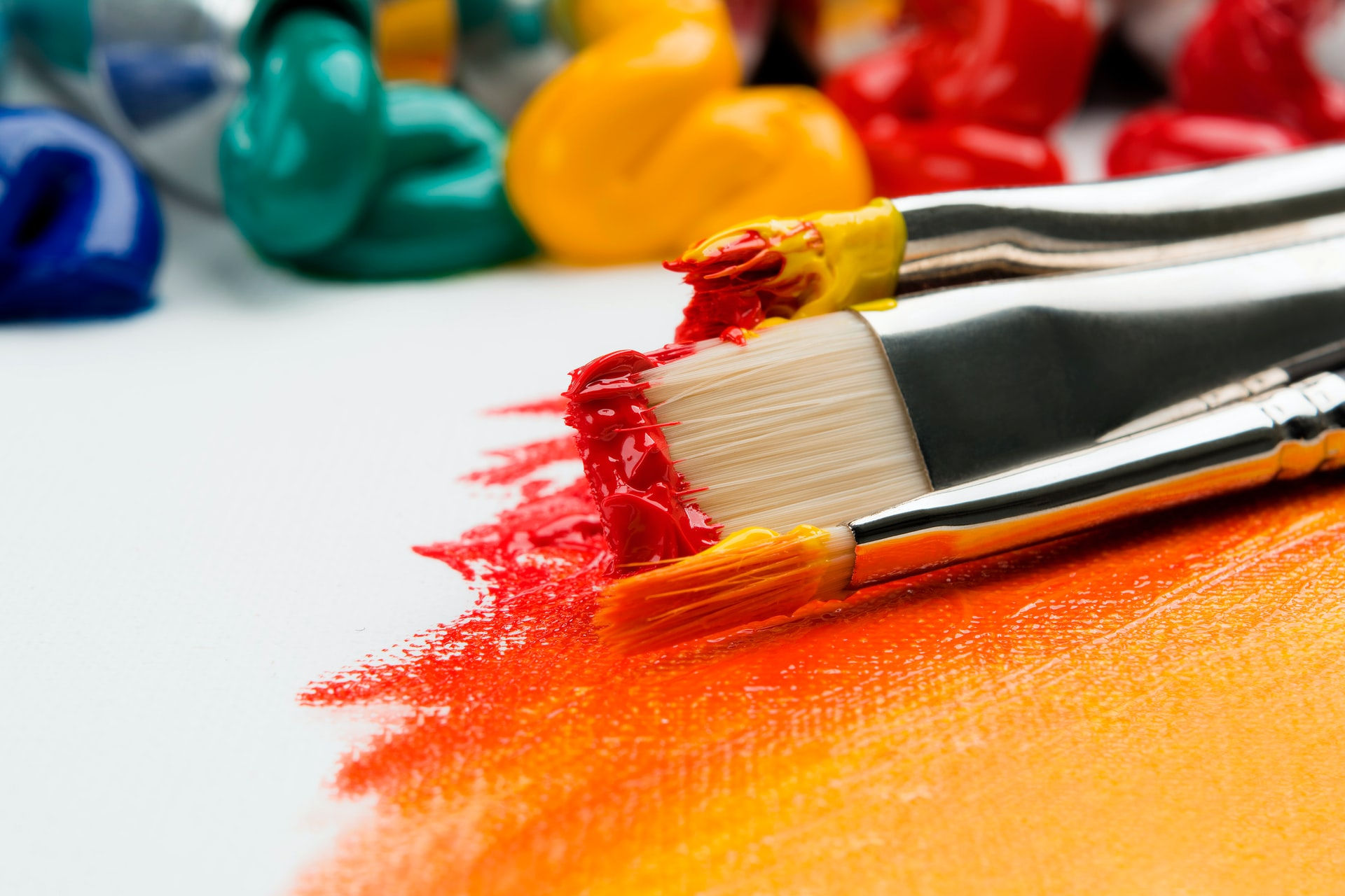 On a white canvas, red, orange and yellow paints have been mixed together. On top of the painted section are paintbrushes that are covered in red, orange and yellow paint. Behind them are different pots of coloured paint, like blue and green.