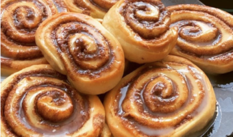 This image shows a number of cinnamon rolls on a plat, they have been layered with a liquid icing sugar.