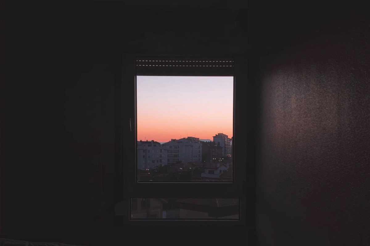 Here we see the inside of a bedroom looking out of a large window with a pink sunset.