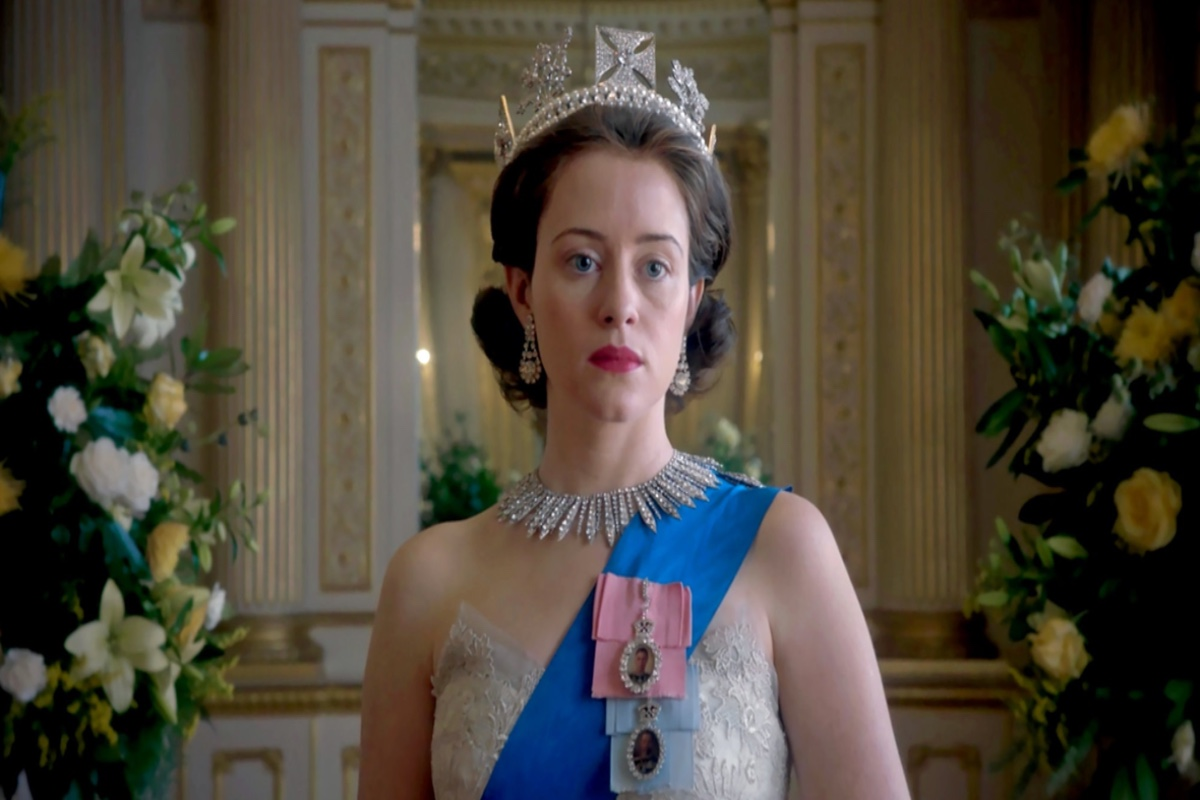 This image shows the character of The Queen in the Netflix series 'The Crown'. She is wearing a strapless dress fitted with lace. A blue ribbon with 2 lockets hanging, a diamond necklace and earring set and a large silver crown.