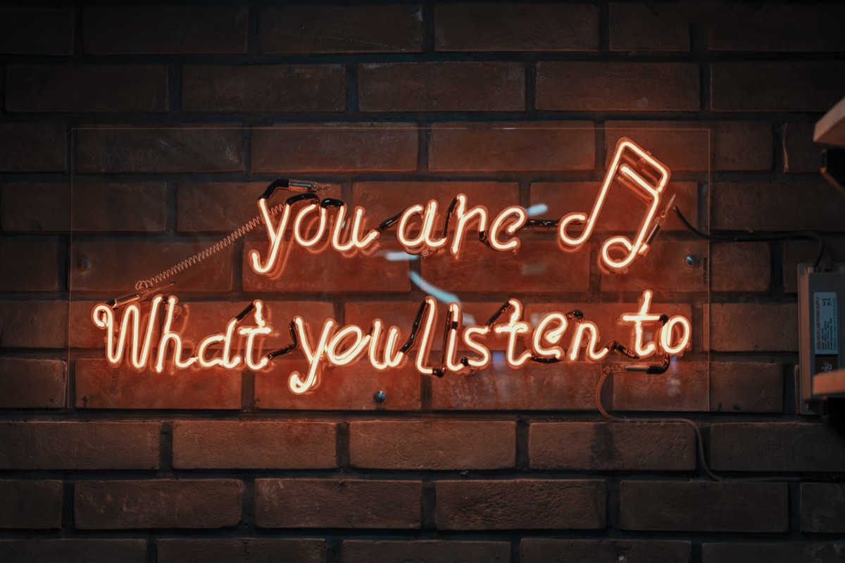"This image shows the sentence ""you are what you listen to"" as a red, light sign."