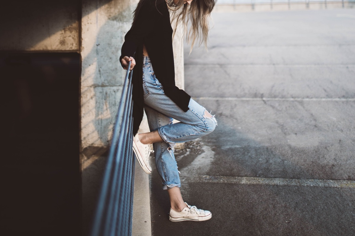 This image shows a girl wearing mom jeans and a large black top with a split down the side. She is rested against a railing with one foot against it.