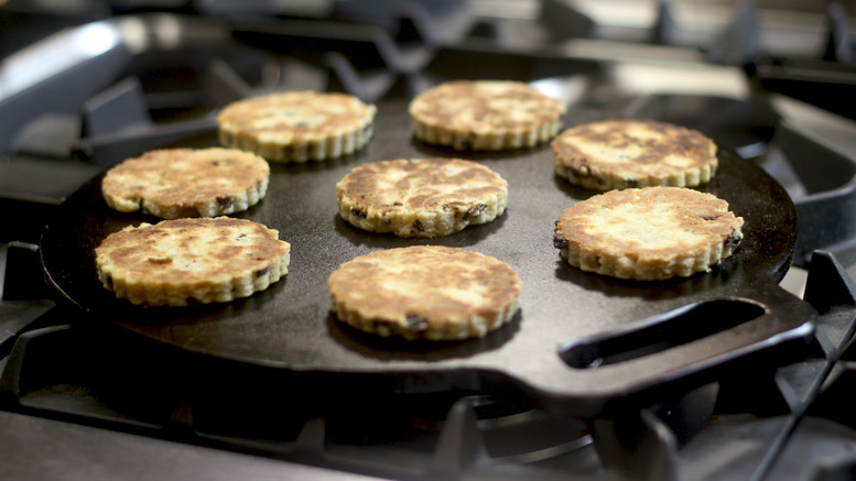 Seven welshcakes sit on a black surface as they are freshly baked and perfectly golden.