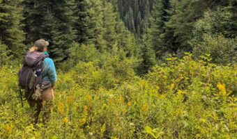 Kelsey Bernard is stood in a bright blue coat and wearing a backpack. She is stood in long grass, facing a large forest