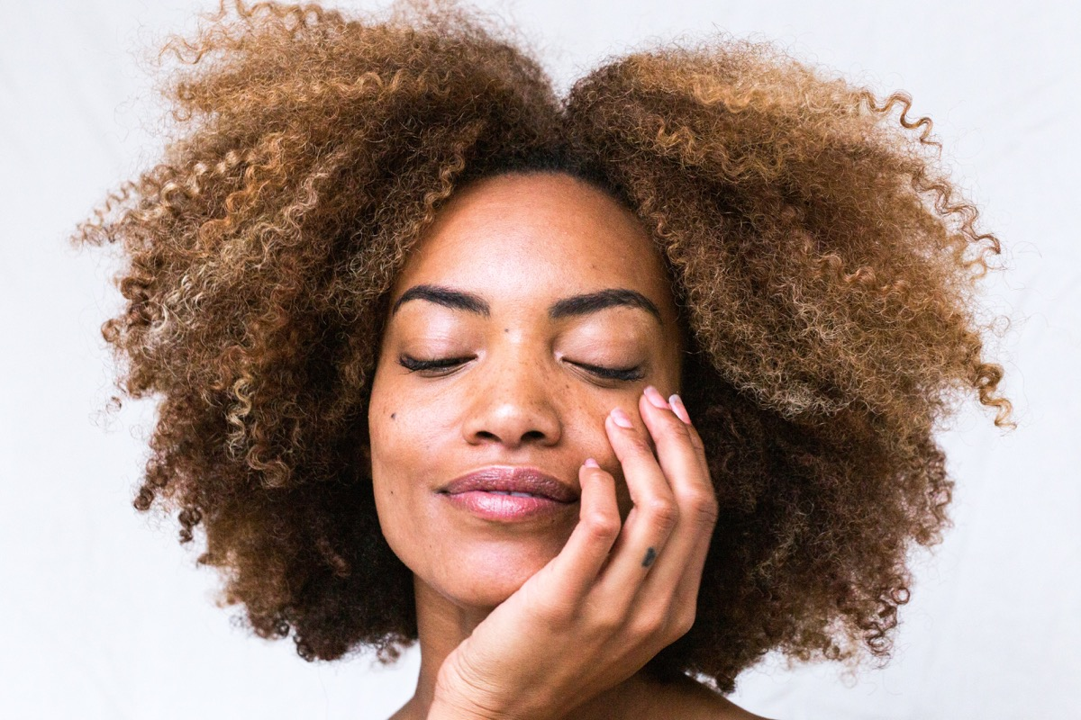 This image shows a woman holding her face with one hand. The woman has an afro with a middle parting.