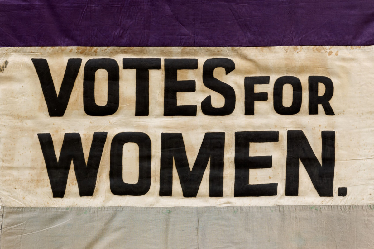 This image shows the bold text reading 'Votes for Women' on a piece of purple, cream and white fabric.