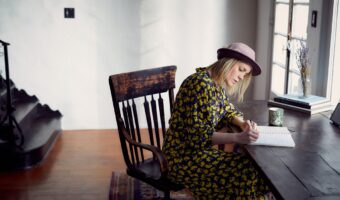 This image shows a woman sat at a desk writing in a book. She is wearing a yellow and black dress and a bowler style hat.