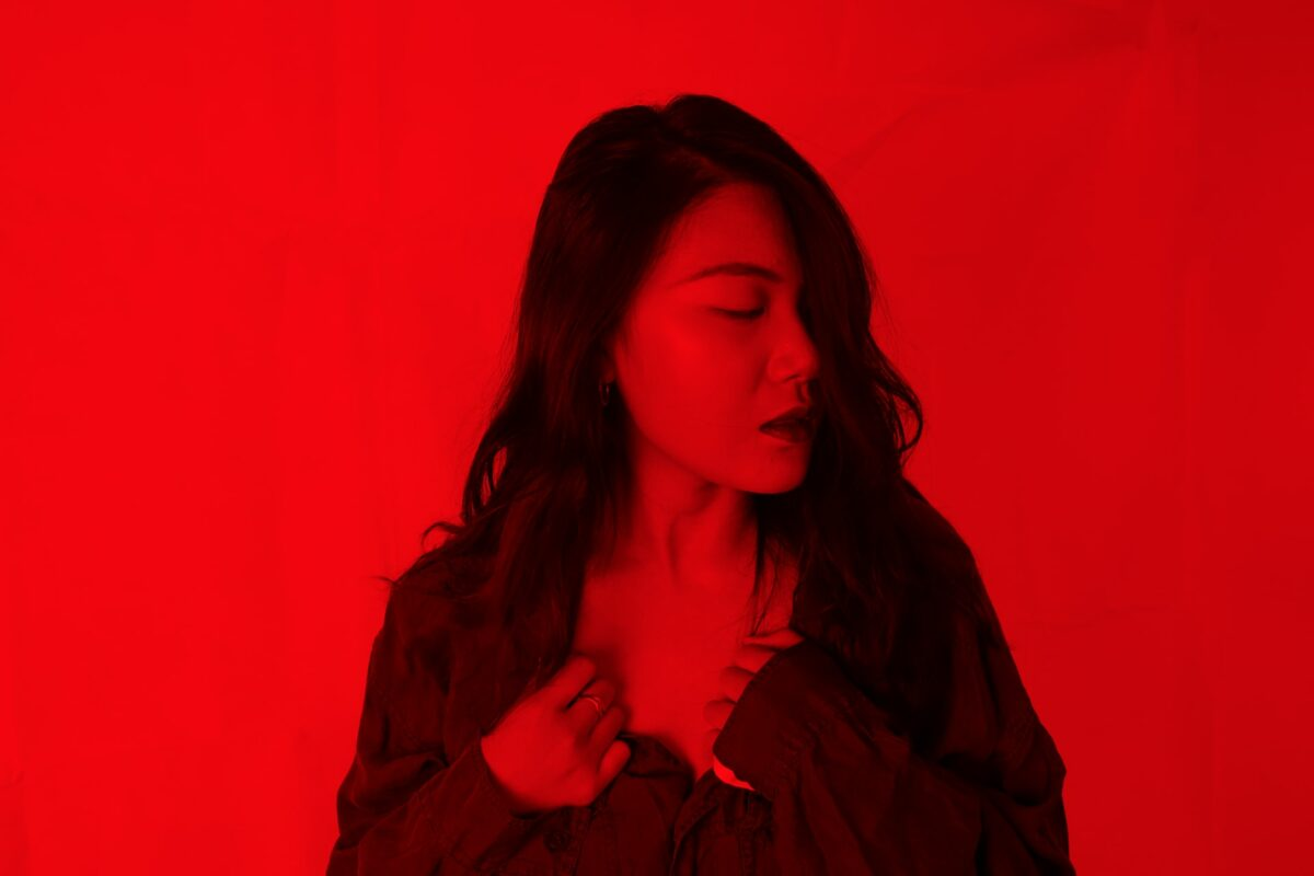 This image is of a lady as she looks to the side with her hands holding the collar of her shirt. The room is light with red lighting.