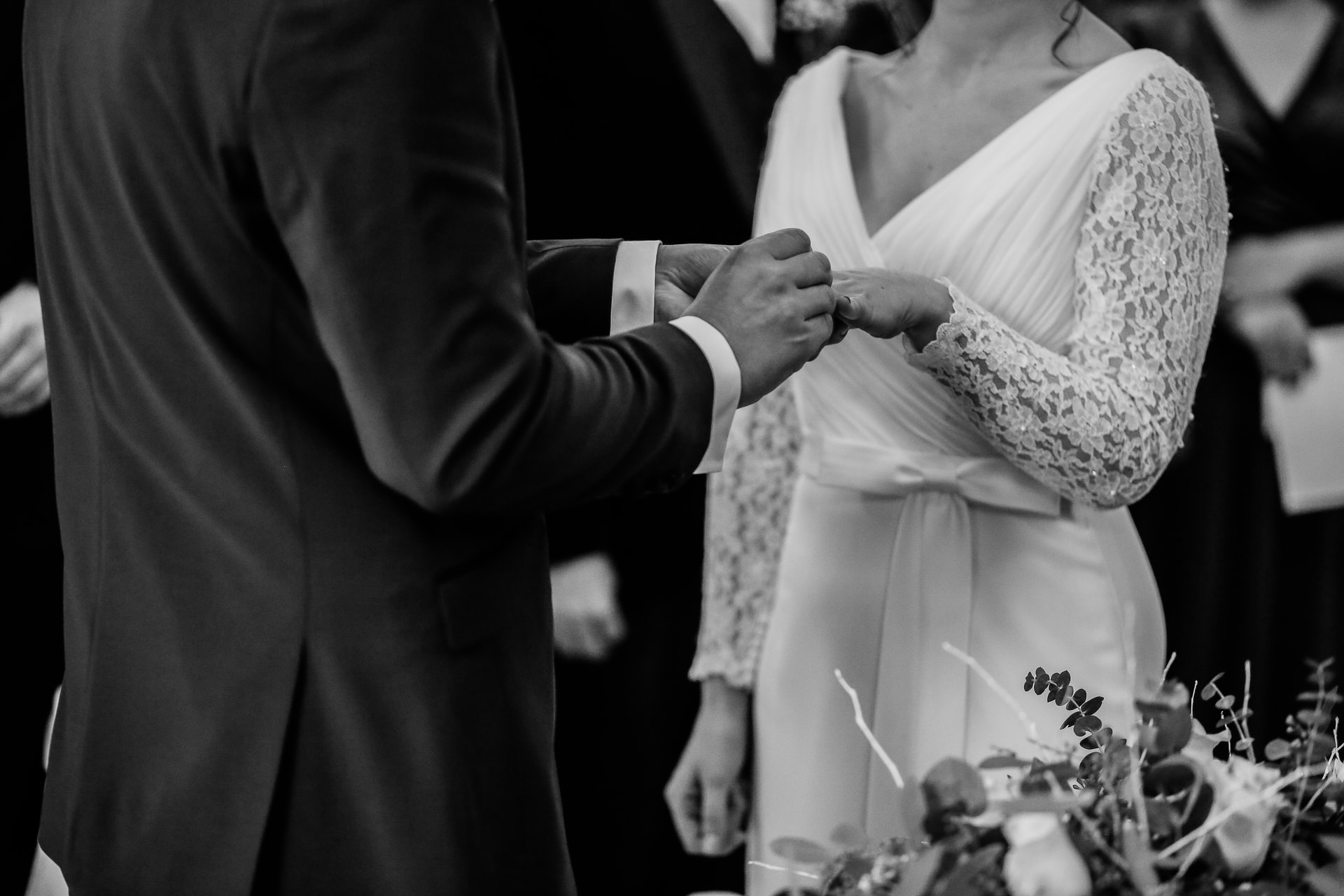This is a black and white image of a groom and his bride as they hold hands during a marriage ceremony.