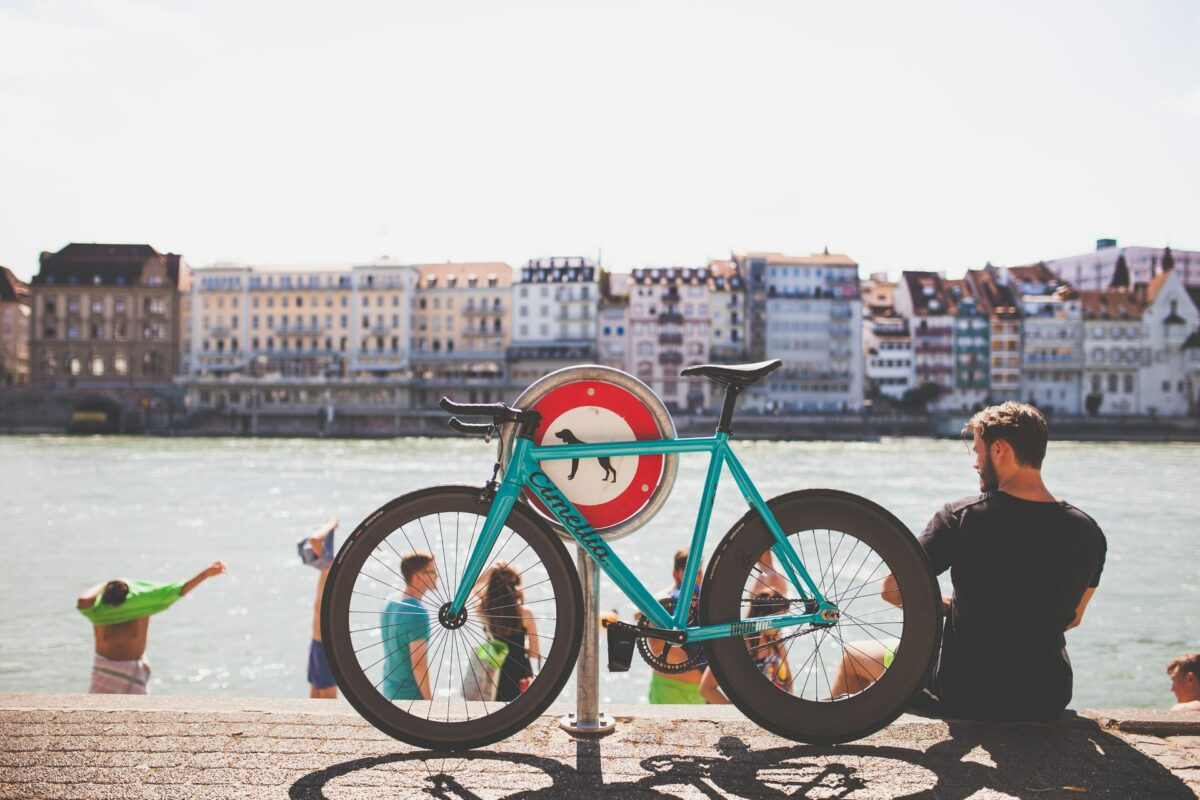 A man sits with his bike propped up as he looks over Basel's River Rhine.