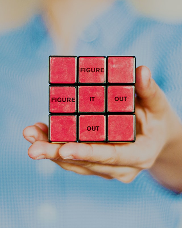 Someone is holding a Rubix cube that has an all red side. on some of the smaller cube faces, it says 'figure it out'.