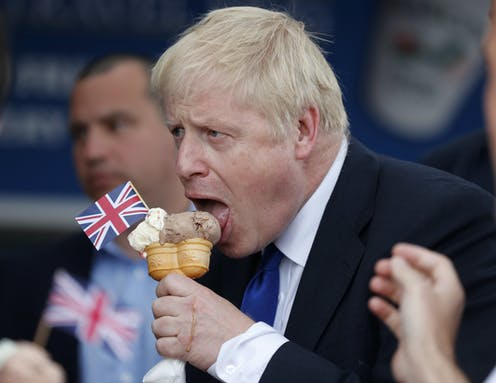 This image shows Boris Johnson licking a ice cream with a mini union jack flag stuck in it.