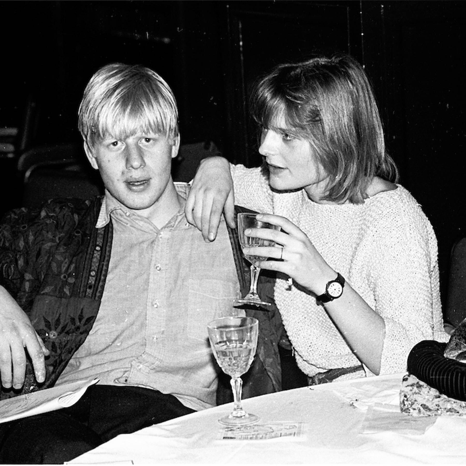 This image shows a young Boris Johnson with his first wife, Allegra Mostyn-Owen as they hold drinks. Boris gazes at the camera as Allegra speaks in his ear.
