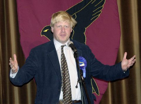 This image shows Boris Johnson speaking into a microphone with his hands up in Henley, 2001.