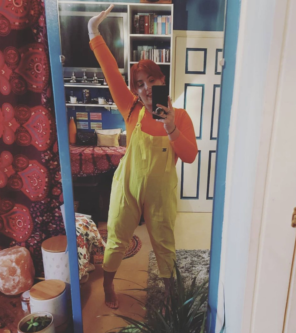 This is a photo that Natalie took in the mirror. She has one arm in the air wearing yellow dungarees.