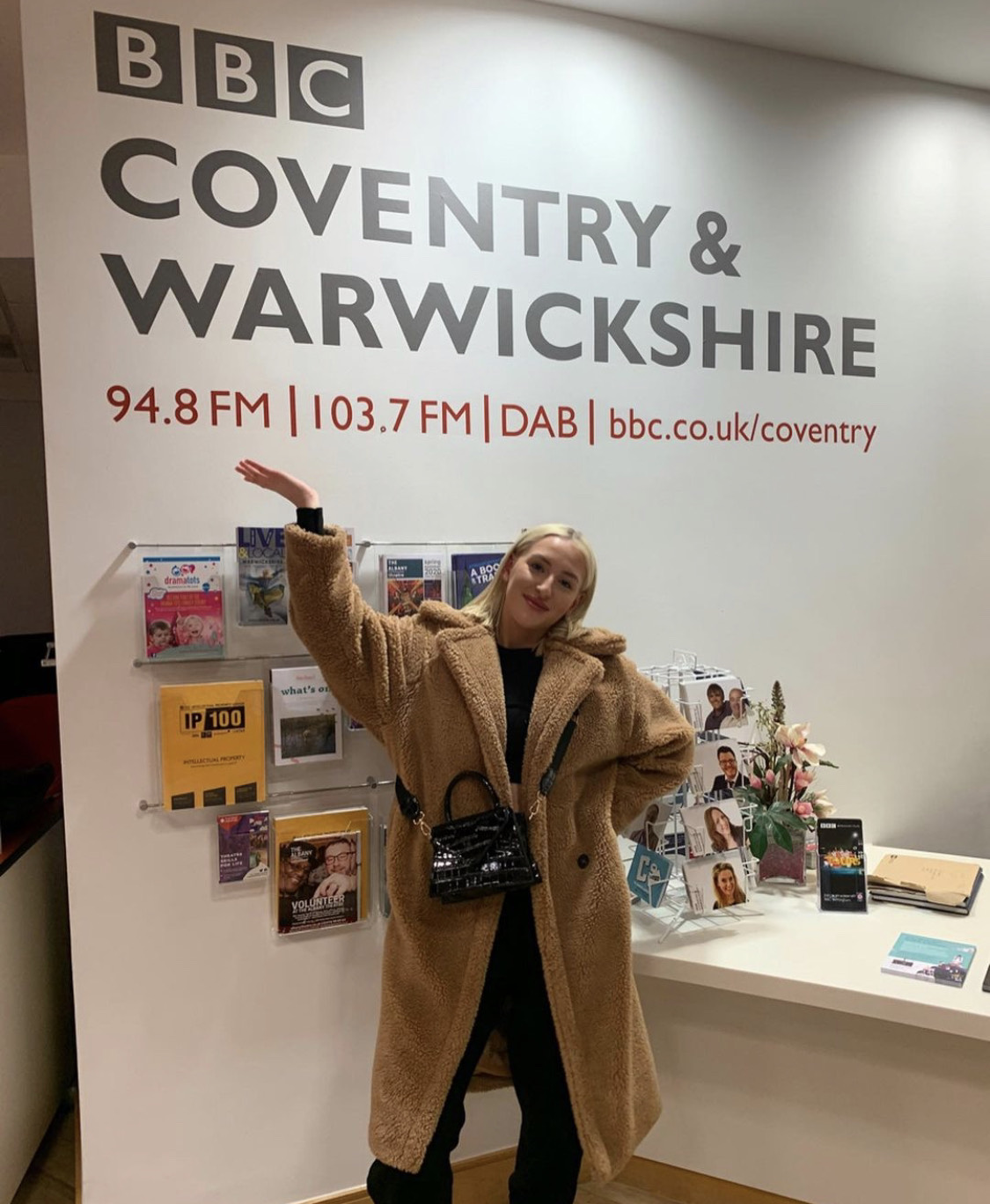 Alise Murray stands infront of BBC Coventry and Warwichshire sign with a teddy bag jacket on after securing a role as a radio presenter/ DJ.
