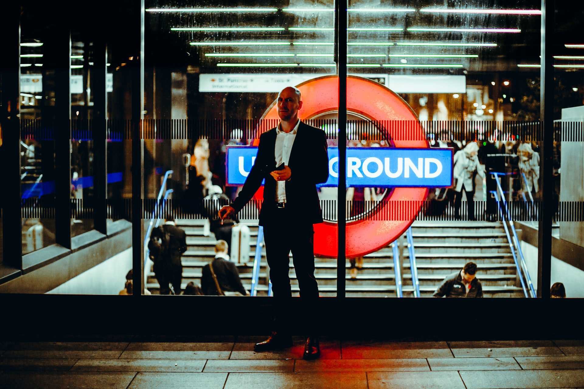 This image shows the neon underground lights from London. Standing infront of the Underground sign is a man in a full formal suit.