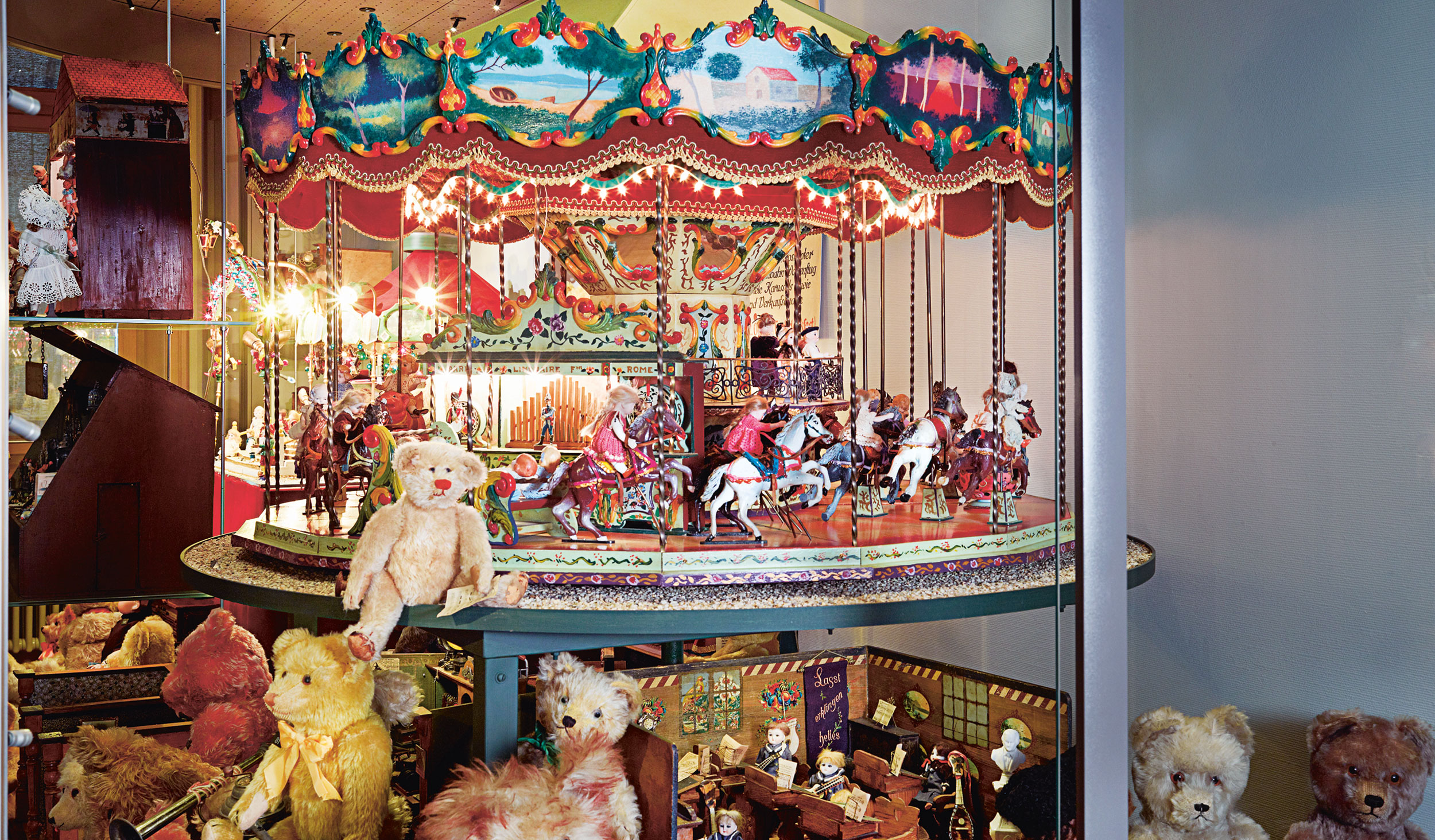 This image shows a toy Carousel wheel with old and dated toys and teddys around.