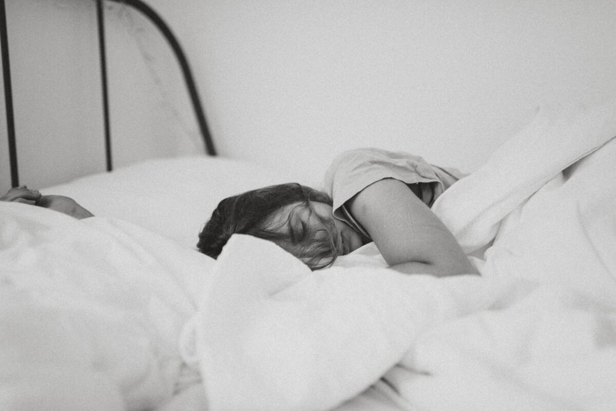 This black and white image shows a girl with dark hair tucked under her crisp white duvet as she sleeps.