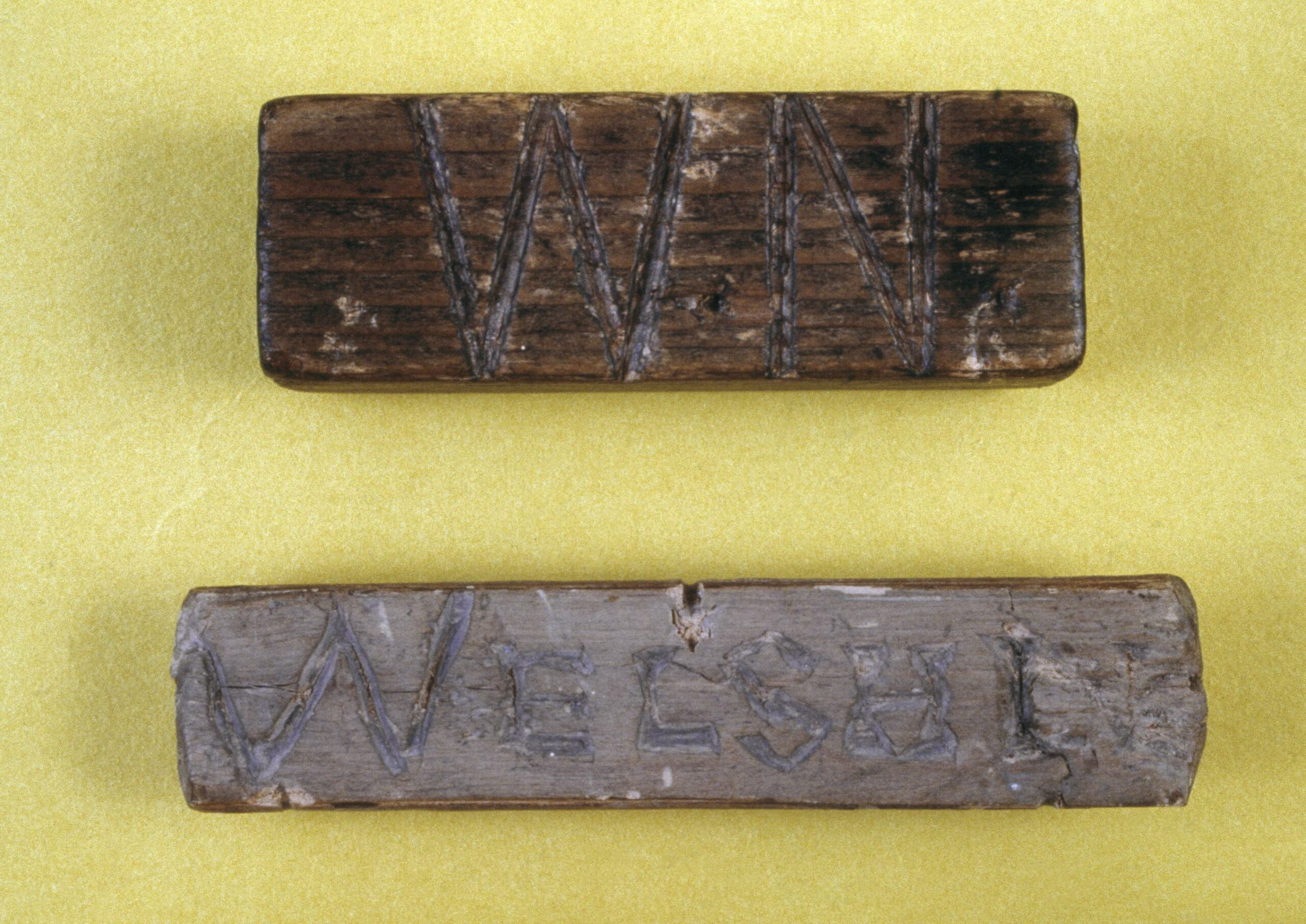 This image shows two dated old wooden planks on a yellow surface. reading 'WN' meaning Welsh Not.